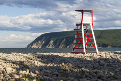 Ingonish Beach and Cape Smokey. A lifeguard chair on rocky Ingonish Beach, with Cape Smokey in the background in the Cape Breton Highlands, Nova Scotia Royalty Free Stock Photo