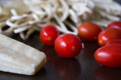 Ingrédients crus des pâtes italiennes avec la tomate et le parmesan photo stock