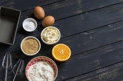 Ingrédients crus - farine, oeufs, beurre, sucre, orange - pour faire cuire le gâteau orange Ingrédients pour le traitement au fou Image libre de droits
