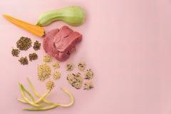 Ingrédients crus naturels pour l'aliment pour animaux familiers sur le fond rose Photographie stock libre de droits