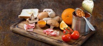 Ingrédients crus pour faire cuire le petit déjeuner anglais sur le boa de cuisine Image stock
