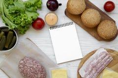 Ingrédients d'hamburger et bloc-notes vide sur le fond en bois blanc, vue aérienne Configuration plate, d'en haut, vue supérieure photographie stock libre de droits