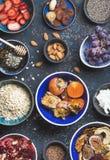 Ingrédients dans des cuvettes pour le petit déjeuner sain au-dessus du fond bleu-foncé Images stock
