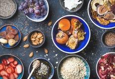 Ingrédients dans des cuvettes pour le petit déjeuner sain au-dessus du fond bleu-foncé Image libre de droits