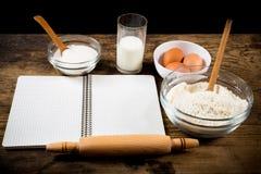 Ingrédients de cuisson et livre de cuisinier sur la table image libre de droits