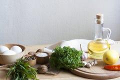 Ingrédients de nourriture Pétrole, oeufs, ail et herbes sur la table en bois Photographie stock