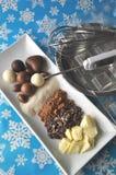 Ingrédients et outils pour faire des chocolats sur le fond d'hiver avec des flocons de neige image stock