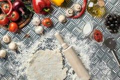 Ingrédients et pâte pour faire les pizzas avec une vue aérienne sur les monticules récemment mélangés de la pâtisserie, un pot d' Photos libres de droits
