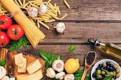 Ingrédients pour des spaghetti avec le basilic, tomates, fromage sur le fond en bois, vue supérieure, endroit pour le texte image libre de droits