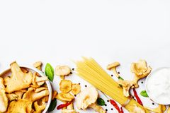 Ingrédients pour faire cuire des pâtes avec des chanterelles de champignons dans le C.A. images stock