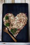 Ingrédients pour faire cuire le petit déjeuner sain dans une forme de coeur Les écrous, flocons d'avoine, ont séché des fruits, m photo libre de droits