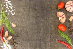 Ingrédients pour faire cuire (tomates-cerises, mauvaise herbe d'aneth fraîche, ail, sel, poivre noir) sur le fond en bois foncé photographie stock libre de droits