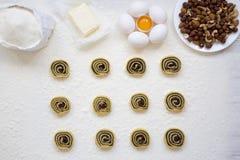 Ingrédients pour faire des biscuits, des biscuits non cuits avec des clous de girofle, des raisins secs et des écrous sur la tabl Photographie stock