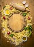 Ingrédients pour faire des pâtes, farine, oeufs, goupille, herbe, huile d'olive, autour de planche à découper sur la vue supérieu Image libre de droits