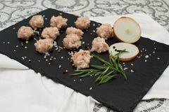 Ingrédients pour faire la soupe avec des boulettes de viande viande crue, oignons et nouilles sur un conseil en pierre noir photo stock