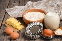 Ingrédients pour faire - lait, beurre, oeufs et farine Fond rustique Photos stock