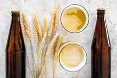 Ingrédients pour la bière Orge à malter près des verres de bière sur la vue supérieure de fond gris Photographie stock