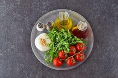 Ingrédients pour la salade caprese italienne traditionnelle sur un trey en verre sur un fond gris avec des bouteilles d'huile d'o Photos stock