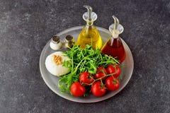 Ingrédients pour la salade caprese italienne traditionnelle sur un trey en verre sur un fond gris avec des bouteilles d'huile d'o Images stock