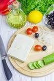 Ingrédients pour la salade grecque sur la planche à découper et la table photo libre de droits