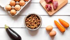 Ingrédients pour la vue supérieure holistique d'aliment pour animaux familiers sur le fond en bois photographie stock