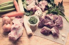 Ingrédients pour le bouillon de viande avec la couleur de ton verte de petit morceau de sauce dedans i Photo stock