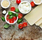 Ingrédients pour le lasagne : basilic frais, tomates-cerises, mozz de bébé Photos libres de droits