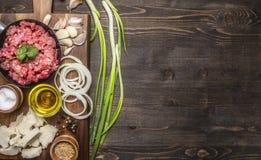 Ingrédients pour les hamburgers faits maison aux oignons et à l'ail, présentés sur un hachoir avec une frontière d'oignons verts, Photos libres de droits