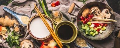Ingrédients végétariens de sauté : légumes coupés, épices, lait de noix de coco, sauce de soja, wok et baguettes, vue supérieure, photo stock