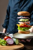 Ingrédients volants d'hamburger ou de cheeseburger au-dessus du plat dans la main de l'homme sur un fond foncé Hamburger flottant image libre de droits