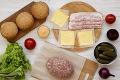 Ingr?dients de cheeseburger sur une surface en bois blanche, vue sup?rieure A?rien, d'en haut, configuration plate Plan rapproch? image stock