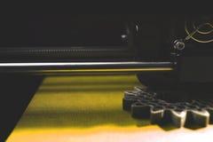 Ingranaggi cilindrici di fabbricazione di FDM 3D-printer dal filamento argento-grigio su nastro giallo della stampa Fotografie Stock