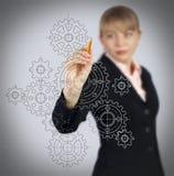 Ingranaggi del disegno della donna di affari sullo schermo fotografie stock