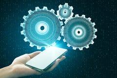 Ingranaggi dello smartphone della tenuta della mano fotografia stock libera da diritti