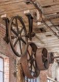 Ingranaggi e pulegge su un soffitto in vecchio magazzino immagine stock