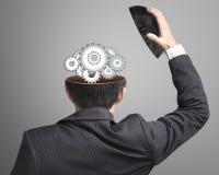 Ingranaggi funzionanti del metallo dentro la testa dell'uomo d'affari Fotografia Stock