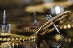 Ingranaggi metallici d'annata nocivi dell'orologio su una superficie nera Fotografia Stock