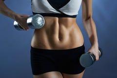 Ingranaggio d'uso femminile di allenamento che tiene i pesi Immagine Stock