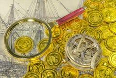 Ingrandica la bussola di vetro su una moneta dorata del pirata Fotografie Stock Libere da Diritti