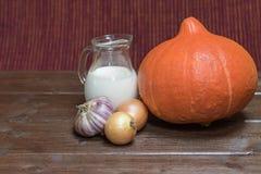 Ingrediënten aan het koken van romige pompoensoep op de houten lijst Stock Fotografie