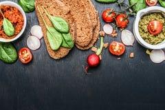 Ingrediënten en uitgespreid voor vegetarische sandwich die op donkere houten achtergrond maken stock afbeeldingen