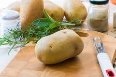Ingrediënten om braadstukaardappels te maken: zout, rozemarijn, salie, boter, kruiden Stock Afbeeldingen