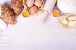 Ingrediënten voor bakselcroissants - de bloem, houten lepel, deegrol, eieren, eierdooiers, boter diende op witte achtergrond Royalty-vrije Stock Afbeeldingen