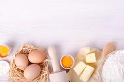 Ingrediënten voor bakselcroissants - de bloem, houten lepel, deegrol, eieren, eierdooiers, boter diende op witte achtergrond Royalty-vrije Stock Foto