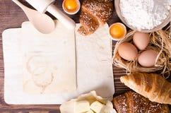 Ingrediënten voor bakselcroissants - het document, bloem, houten lepel, deegrol, eieren, eierdooiers, boter diende op een plattel Stock Fotografie