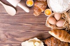 Ingrediënten voor bakselcroissants - het document, bloem, houten lepel, deegrol, eieren, eierdooiers, boter diende op een plattel Stock Foto