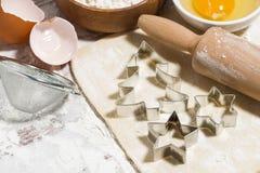 Ingrediënten voor de koekjes van bakselkerstmis op lijst Deeg, koekjessnijders en deegrol, close-up royalty-vrije stock foto's