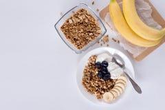 Ingrediënten voor eigengemaakte havermeelgranola in glaskruik Havervlokken, honing, rozijnen en noten Gezond ontbijtconcept met e Stock Afbeelding