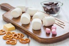 Ingrediënten voor eigengemaakte Kerstmiszoetheid: heemst, chocolade, pretzel, houten stokken stock afbeeldingen