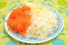 Ingrediënten voor het koken van een salade van geraspte kaas en gekookte eieren op een plaat op de keukenlijst Stock Foto's